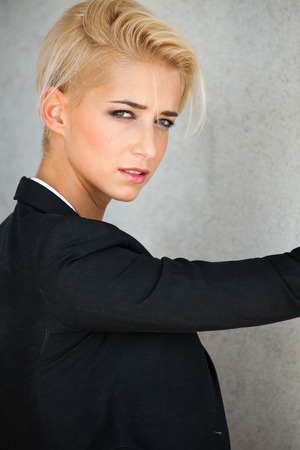 black hair blue eyes: young blue eyes woman with trendy short blonde hair in black blazer outdoor portrait