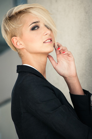 blazer: smiling young blue eyes woman with short blonde hair in black blazer outdoor portrait