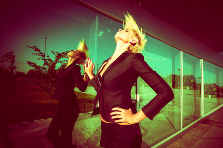 short back: elegant young  woman with short blonde hair in black blazer throw back hair shot in the city by the glass wall