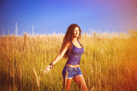 smiling beautiful woman with long curly hair stand in grass field photo