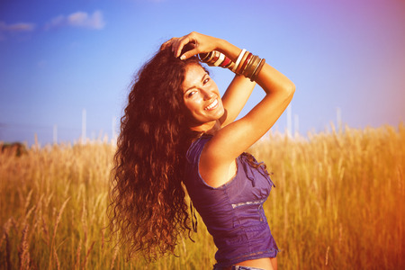 smiling beautiful woman with long curly hair enjoy in sun and nature  in grass field photo
