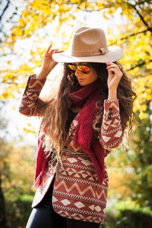 帽子、サングラス、コート、赤いスカーフを身に着けている長い巻き毛を持つ若い女性は、秋の晴れた日に公園でお楽しみください。 写真素材