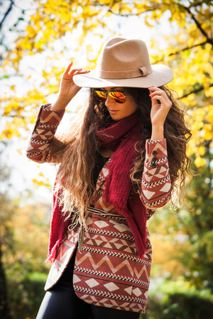young woman with long curly hair wearing hat,  sunglasses, coat and  red scarf enjoy in autumn sunny day in park Foto de archivo