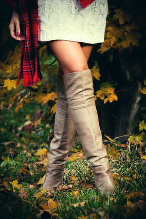 woman wearing white wool dress, red tartan scarf and long leather boots, outdoor shot in autumn park