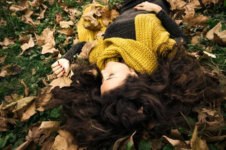 ojos verdes: hermosa mujer con los ojos cerrados se encuentran en la hierba y las hojas de otoño con un vestido de color verde oscuro y una larga bufanda de lana de color amarillo