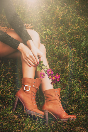 women in boots: woman legs in brown ankle high heel boots sit on grass hold flowers in hands Stock Photo