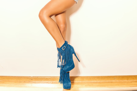 fringe: long slim woman legs in blue  ankle high heel fringe boot indoor shot on parquet against wall