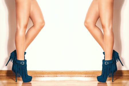 ankles sexy: long slim woman legs in blue  ankle high heel fringe boot indoor shot on parquet against wall