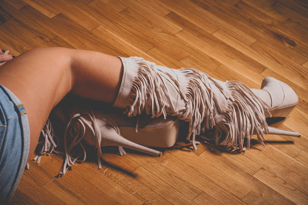 woman legs in high heels long boots on parquet Stock Photo