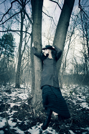 long skirt: blonde woman wearing hat, leather coat and long skirt stand by tree  in the forest, cold winter day, full body shot