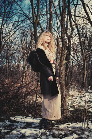 clothing model: blonde woman in coat and long wool dress stand in the forest, cold winter day, full body shot
