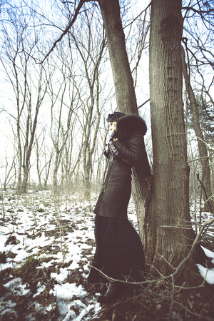desaturated: fashion woman in coat with fur and long skirt stand by tree in winter wood
