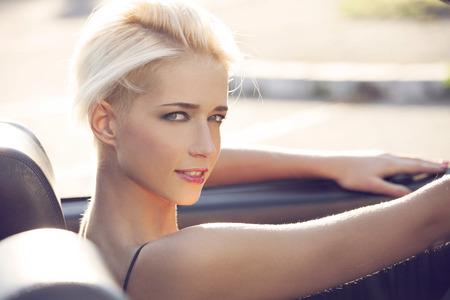 chicas sonriendo: joven mujer rubia en el coche