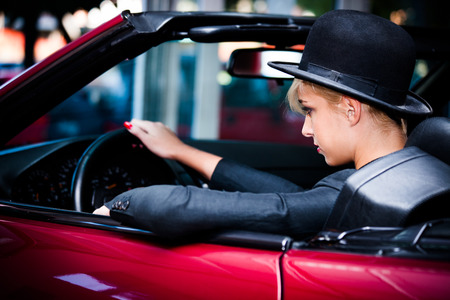 cabrio: young urban fashion woman driving red cabrio through the city Stock Photo