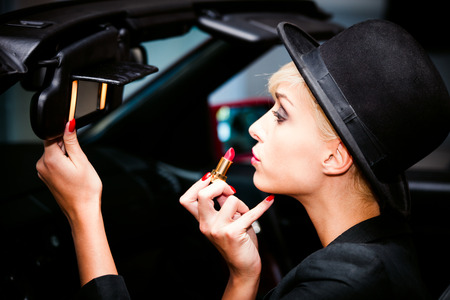 young fashion blonde woman with hat applying red lipstic using car mirror Stockfoto