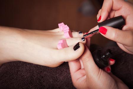 pedicura: Mujer en el sal�n de cosm�ticos de aplicar el esmalte de u�as negro en las u�as Foto de archivo