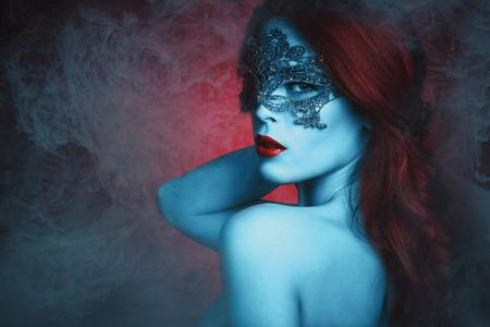 mascaras de carnaval: fantas�a hermosa mujer joven con la m�scara del cord�n, piel azul y el pelo rojo en la neblina
