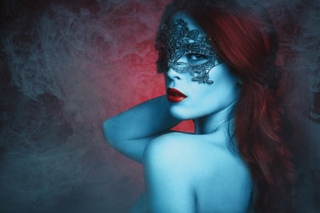 masquerade masks: fantasy  beautiful young woman with lace mask, blue skin and red hair in haze