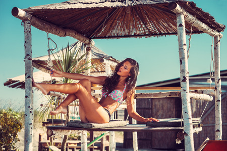 tanned body: young woman in bikini  sit at shade at seaside beach enjoy in summer hot sunny day, full body shot