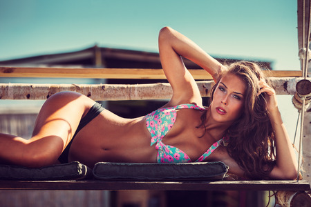 young woman in bikini  lie at shade at seaside beach enjoy in summer hot sunny day