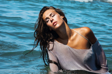enjoy space: attractive young woman in blue sea water, fashion shot, hot summer day