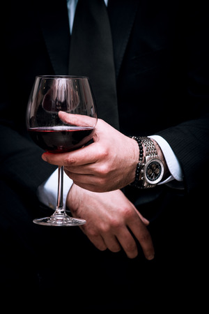 adult elegant man hold glass of red wine, close up, indoor shot, selective focus Standard-Bild