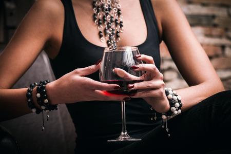 若い上品な女性が赤ワイン、屋内撮影、選択と集中のガラスを保持します。