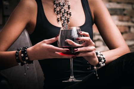 young elegant woman hold glass of red wine, indoor shot, selective focus Stockfoto