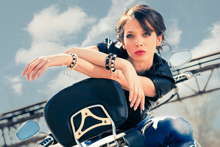 woman short hair: young beautiful woman sitting on motorbike, sunny day outdoor