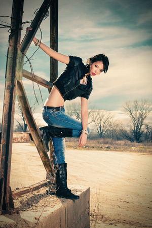 full metal jacket: young rebel woman in blue jeans, leather boots and leather jacket outdoor shot on old metal construction hot sunny day