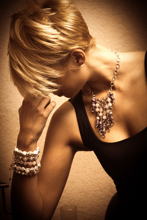 short hair blond elegant young woman portrait wearing jewelry, necklace and lot of bracelets, indoor shot, side view Foto de archivo