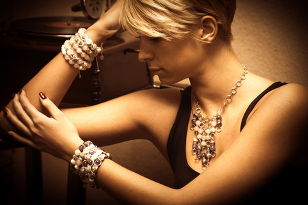 vrouw blond: kort haar blonde elegante jonge vrouw portret dragen van sieraden, ketting en veel armbanden, indoor shot, zijaanzicht Stockfoto