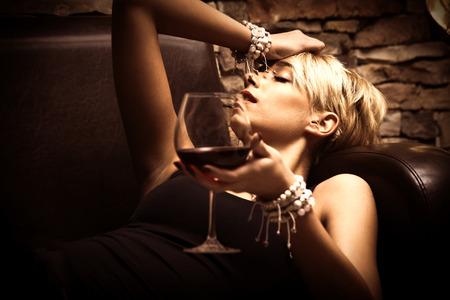 mooie jonge vrouw liggen met een glas rode wijn in de hand, zijaanzicht, close-up, binnen-shot Stockfoto