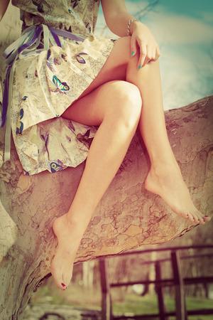 barefoot woman legs, sit on tree in romantic summer dress, retro colors Stock Photo