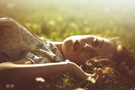 feels: delicate beautiful young woman enjoy in sun lie in grass retro look and colors
