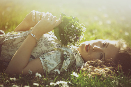 feels: delicate beautiful young woman enjoy in sun lie in grass hold bouquet of wild flowers retro look and colors