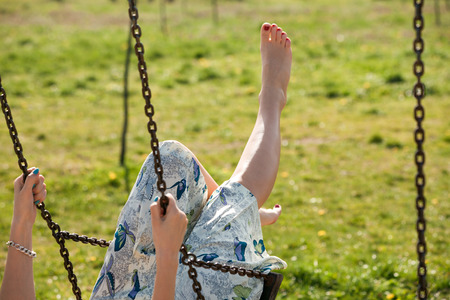 feels: barefoot young woman in dress on swing outdoor in park warm spring day