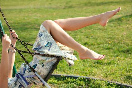 ragazze a piedi nudi: a piedi nudi giovane donna in abito su altalena all'aperto nel parco calda giornata di primavera Archivio Fotografico