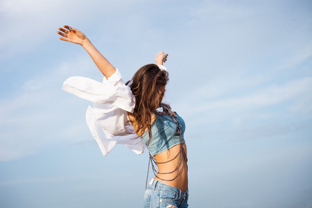young carefree woman with hands up in blue jeans and white shirt in motion against blue sky Stock Photo
