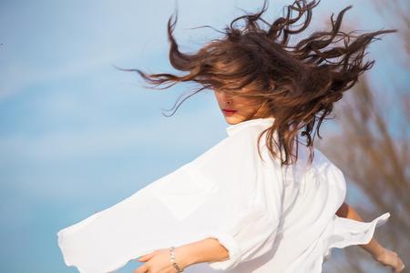 junge Frau im weißen Hemd mit Haar in der Bewegung, im Freien Frühlingstag, blauer Himmel im Hintergrund