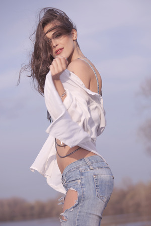 warm shirt: brunette woman in white shirt and jeans, stand on wind with hair fly, warm summer day Stock Photo