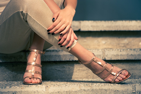 woman legs in high heel golden sandals and pants sit on stairs, outdoor shot, close up Stock Photo