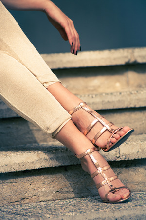 lean on hands: woman legs in high heel golden sandals and pants sit on stairs, outdoor shot, close up Stock Photo