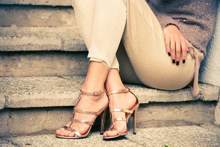 piernas de la mujer en tacón alto sandalias doradas se sientan en las escaleras, tiro al aire libre