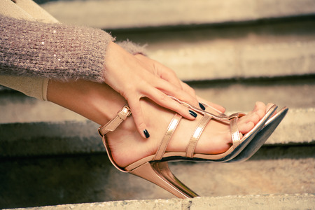 woman legs in high heel golden sandals lean on stairs, outdoor shot, close up Stock fotó