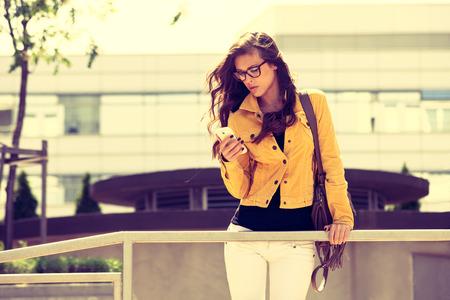 urban colors: Mujer urbana joven con gafas que usa smartphone, tiro al aire libre en la ciudad, colores retro