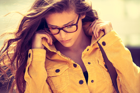 protecting spectacles: young urban woman with eyeglasses portrait,  outdoor shot in the city, retro colors