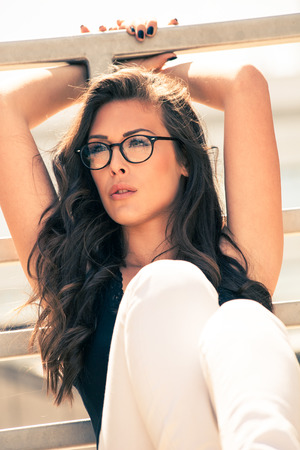 hot pants: young urban woman with eyeglasses portrait,  outdoor shot in the city, sunny day