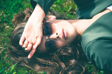 sunglasses: young  urban woman with sunglasses lie in grass,  retro colors