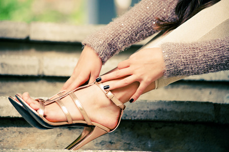 woman sandals: woman legs in high heel golden sandals lean on stairs, outdoor shot, close up Stock Photo